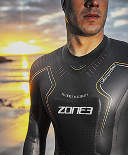 Guy on beach in Zone 3 wetsuit with sunset in background