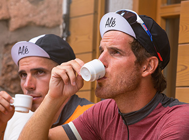 Cyclist enjoying a coffee while wearing an Alé cap. Click to shop this seasons Alé accessories.