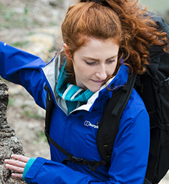 Women stood by rock wearing a blue berghaus jacket