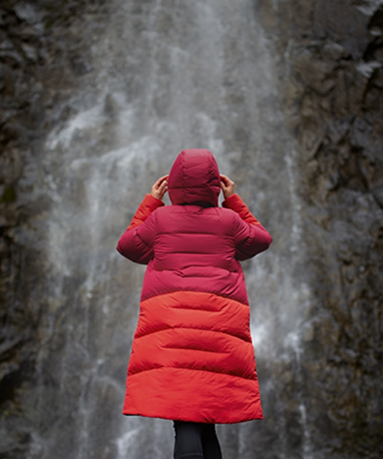Woman stood in front under a waterfall wearing Berghaus combust long jacket