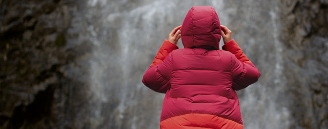 Woman stood in front under a waterfall, wearing Berghaus combust long jacket