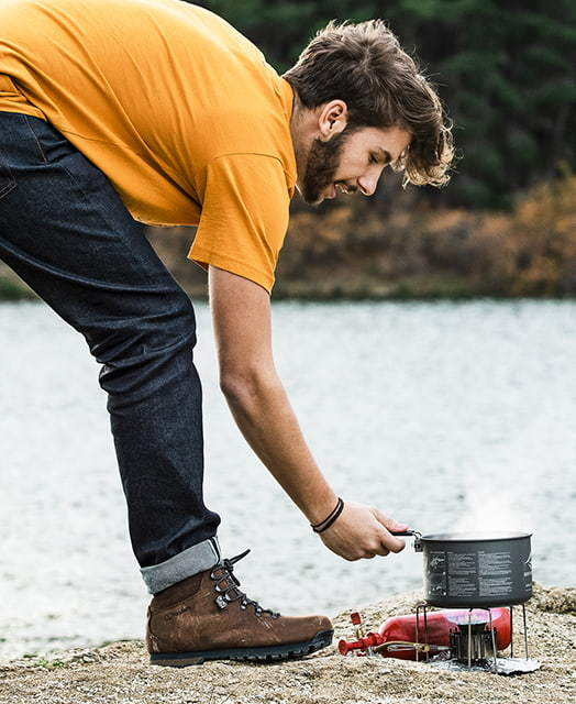 Man cooking outdoors on a portable stove wearing brown walking boots