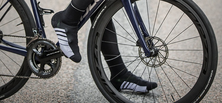Close up of persons' feet clipped into bike, wearing GripGrab shoe covers