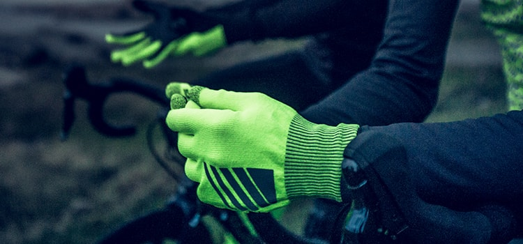 Close up of people on bike, wearing fluro coloured GripGrab gloves at night