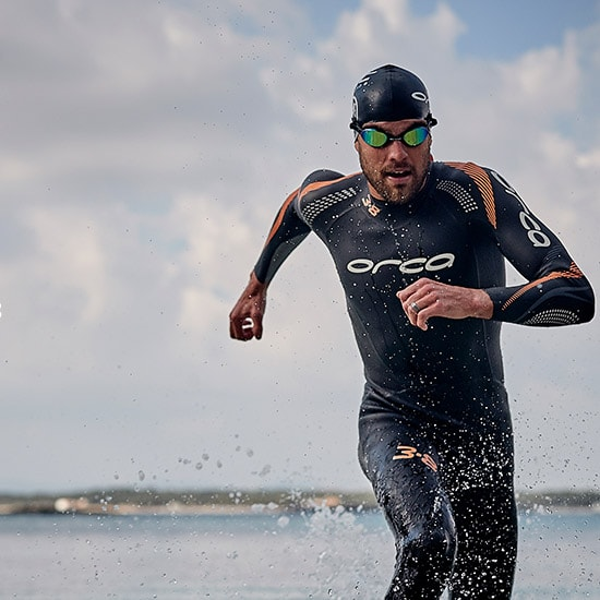 A triathlete runs out of the sea after a hard swim, Wearing the new 3.8 wetsuit from orca.