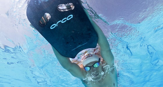 A swimmer swims in a pool using orca equipment to help him train. Click to see the full range of Orca Swimwear & Equipment
