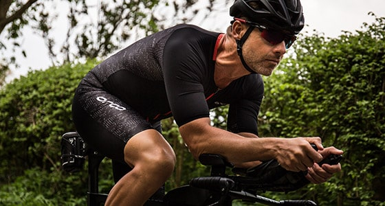 A triathlete rides on his bike wearing an Orca triathlon kit. Click to see more of Orca triathlon specific clothing