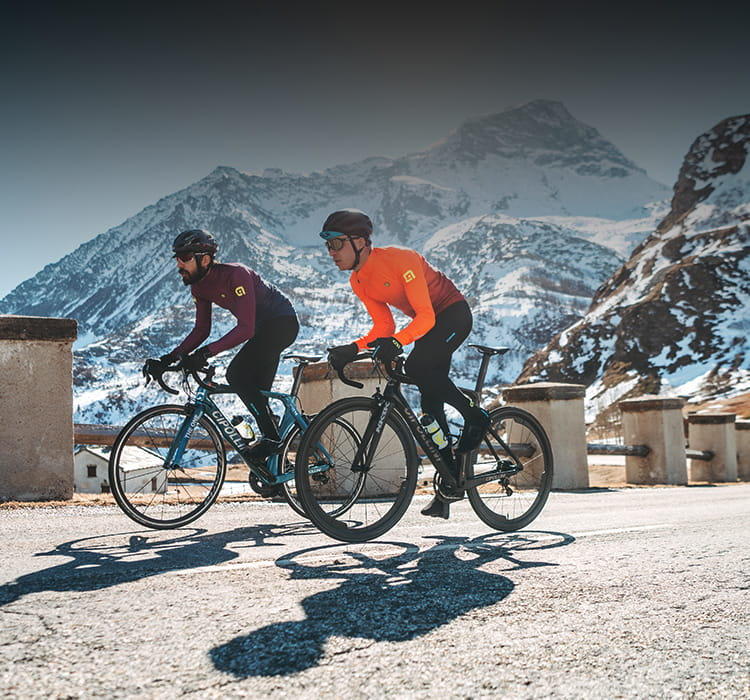 Two men out cycling in the mountains wearing Ale A/W clothing