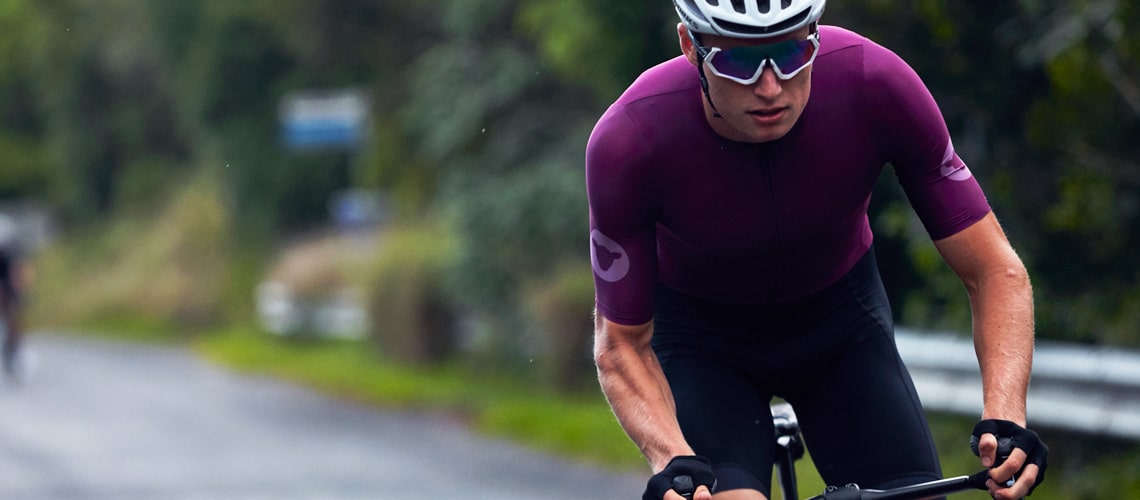 Man in purple blacksheep jersey cycling