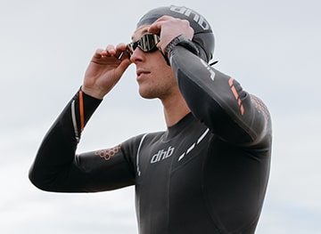 A Triathlete stands ready to swim. Shop D.H.B triathlon wear.