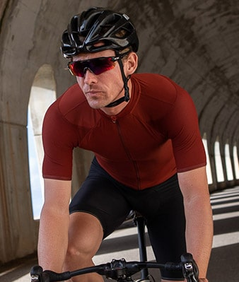 A road cyclist rides in a tunnel, he is wearing a maroon jersey from Isadore.