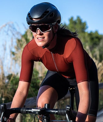 A road cyclist riding on a sunny day, she is wearing a maroon jersey from Isadore.