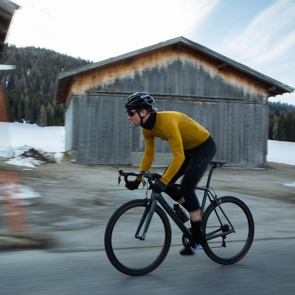 A road cyclist rides in winter weather, he is wearing a yellow jersey from Isadore.