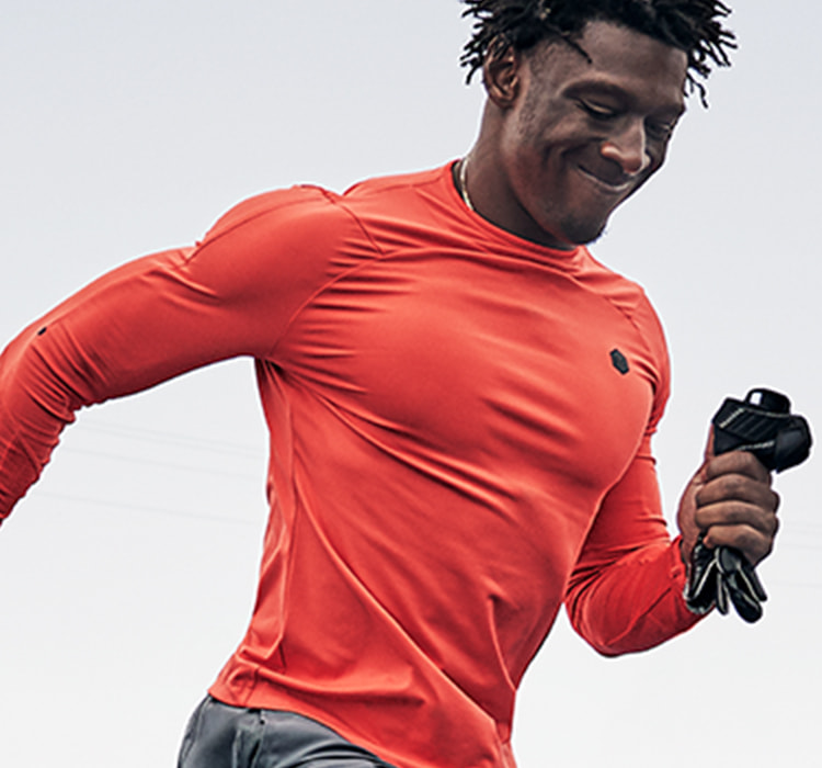 Man outisde training in a red long sleeve Under Armour top