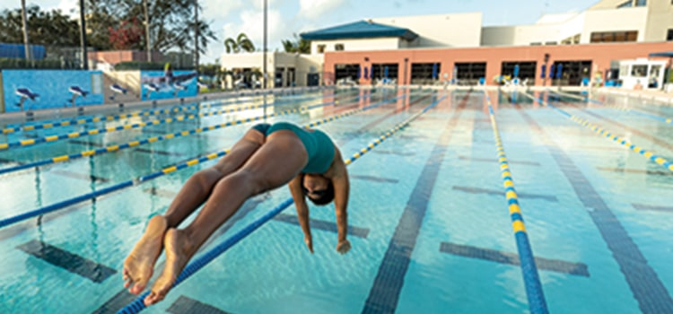 Girl diving into an outdoor swimming pool