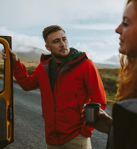 Man wearing red Berghaus jacket talking to friend