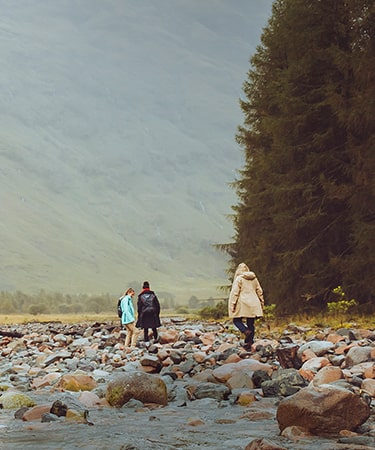 Group of women adventuring near a river whilst wearing waterproof Gore-Tex jackets