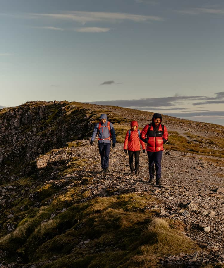 Three people out hiking in the mountains wearing Berghaus winter jackets