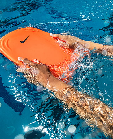Guy in pool swim training with a orange Nike float