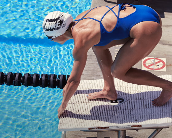 Woman at outdoor swimming pool, getting ready to dive in from the dive board