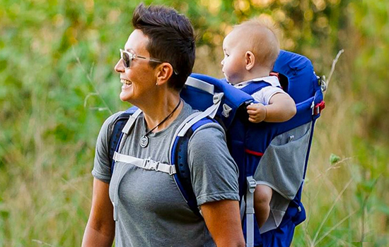 Woman carrying child on her back with Osprey Child Carrier