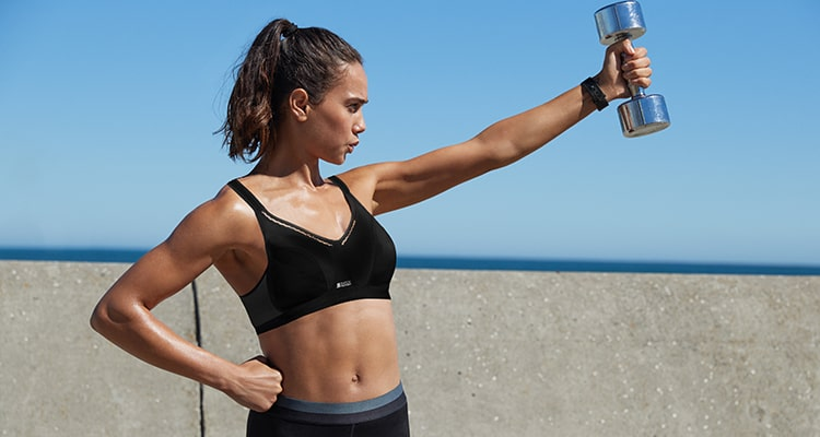 Girl outside lifing dumbells wearing a black Shock Absorber sports bra