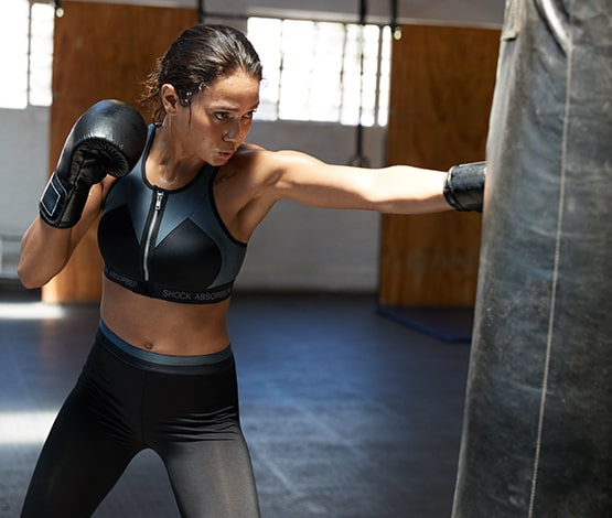 Girl wearing boxing gloves punching a punch bag wearing a Shock Absorber sports bra