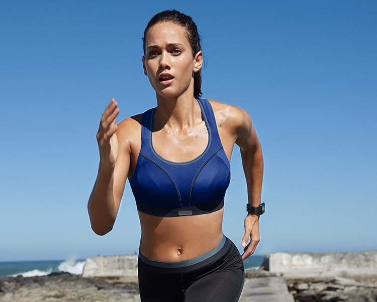 Girl out running wearing a blue Shock Absorber ultimate run bra