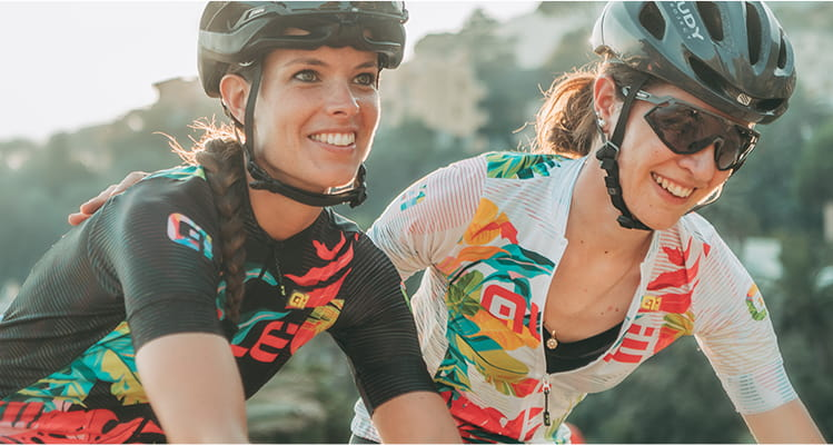 Two women out cycling wearing colourful printed ale jerseys