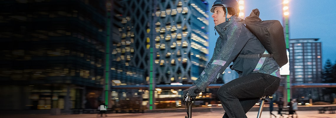 Guy riding bike in dark through city streets, wearing altura cycle kit