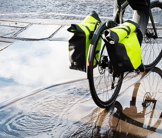 Person riding through a puddle, with altura luggage storage on back of bike