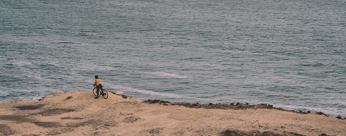 Guy riding bike at a sandy beach