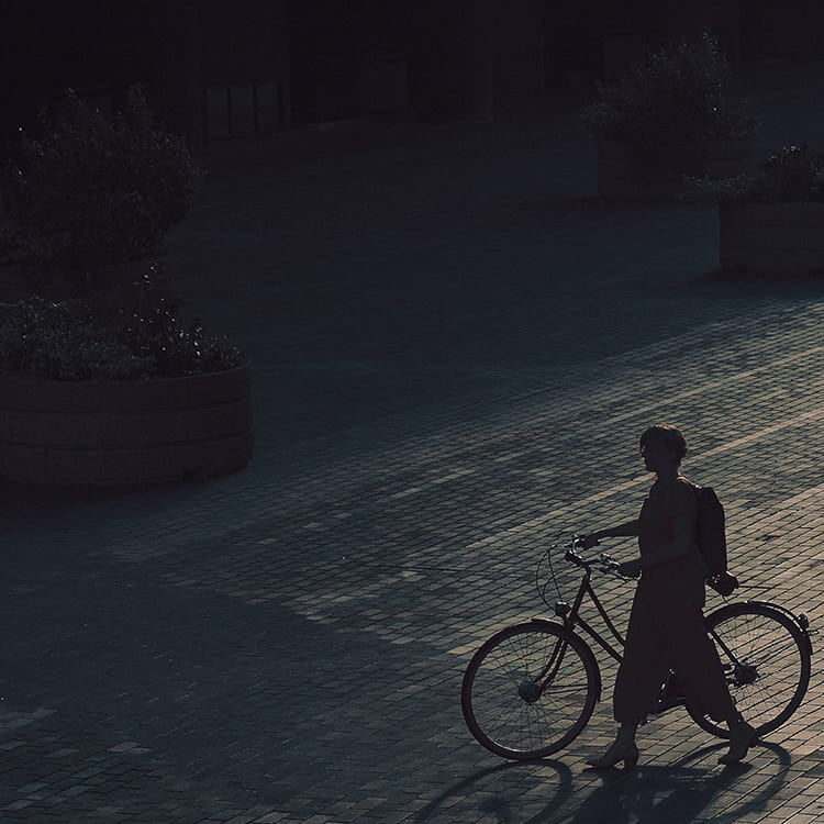 Lady walking along with bike at night time