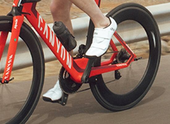 Person riding red bike wearing white dhb shoes