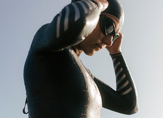 Guy in dhb wetsuit putting his dhb googles on
