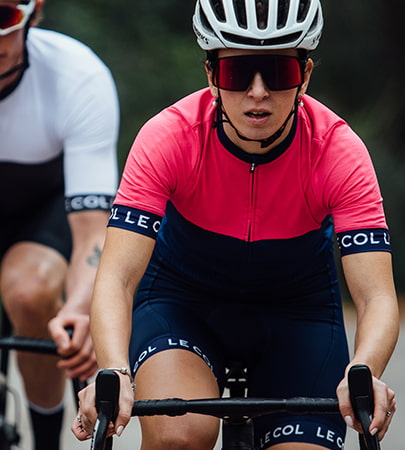 Lady cycling wearing pink and blue Le Col sport cycle kit