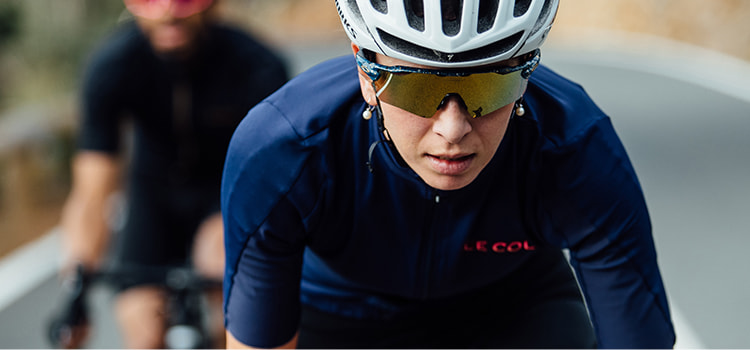 A lady cycling wearing Le Col kit