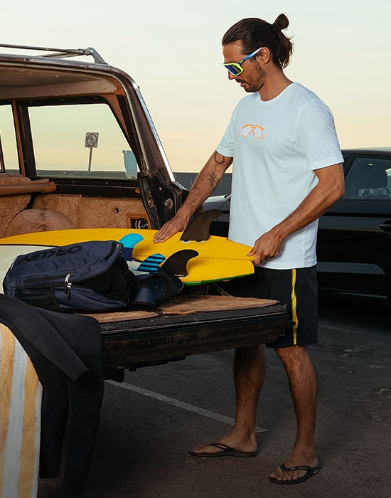 Guy putting surfboard on back of truck wearing causal Oakley clothing