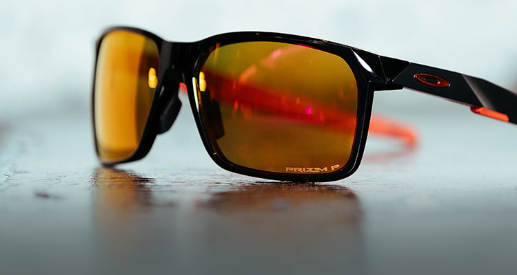 Black Oakley sunglasses with a bright orange lense