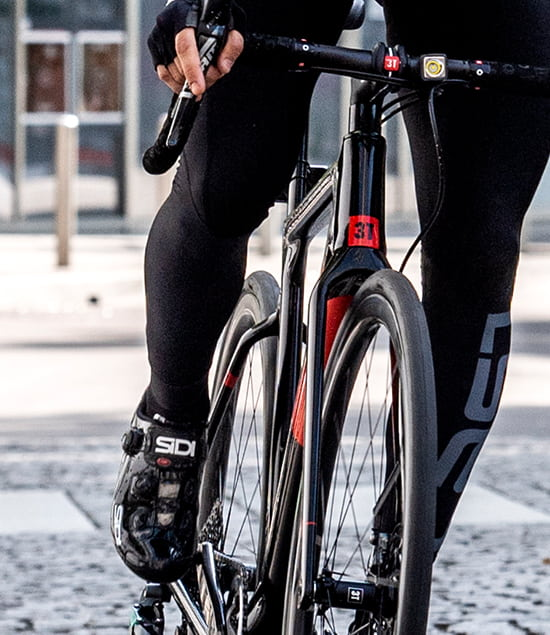 Person riding black and red road bike with pirelli urban tyres