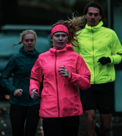 Three people out running in bright reflective Ronhill jackets