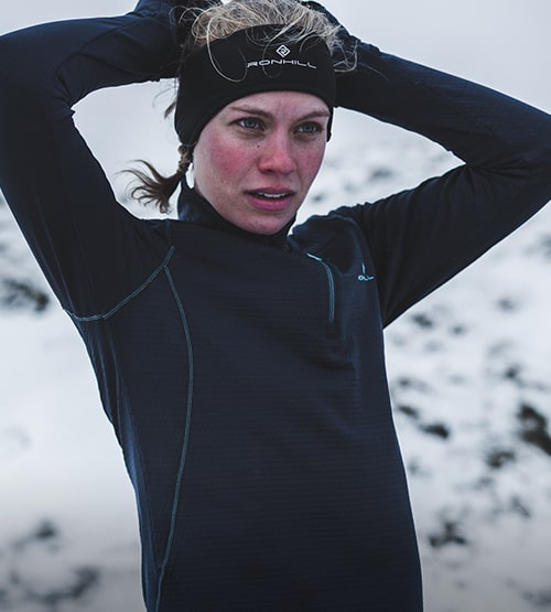 A girl out running in the snow wearing black thermal ronhill gear