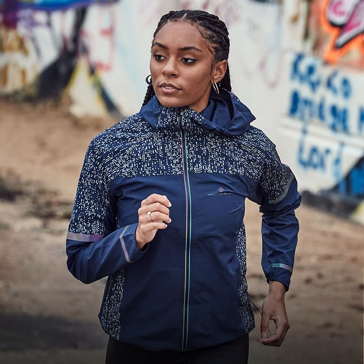 Girl running in the blue Ronhill nighrunner jacket with a graffiti wall in background