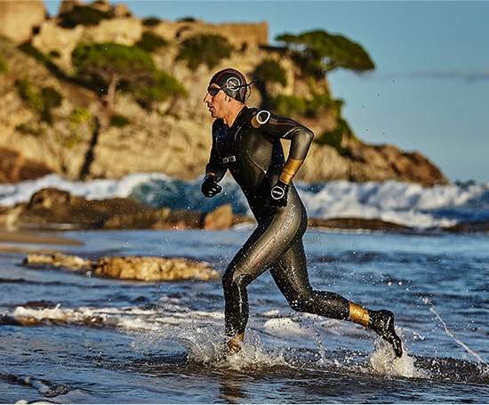 Guy in Zone3 wetsuit running out of the sea