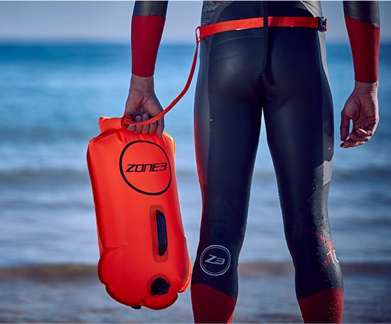 Person stood by side of sea, getting ready for a swim, wearing their Zone3 wetsuit and holding their Zone3 buoy