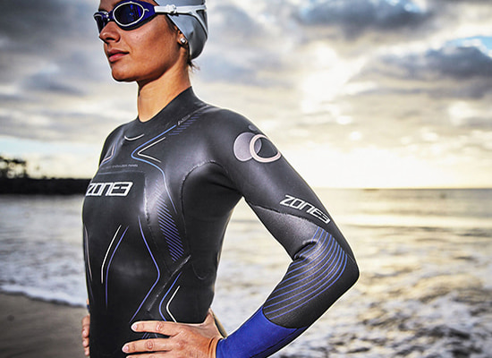 Girl stood by sea, wearing up her Zone3 Aspire wetsuit