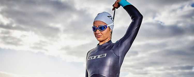 Girl stood by sea, zipping up her Zone3 Azure wetsuit
