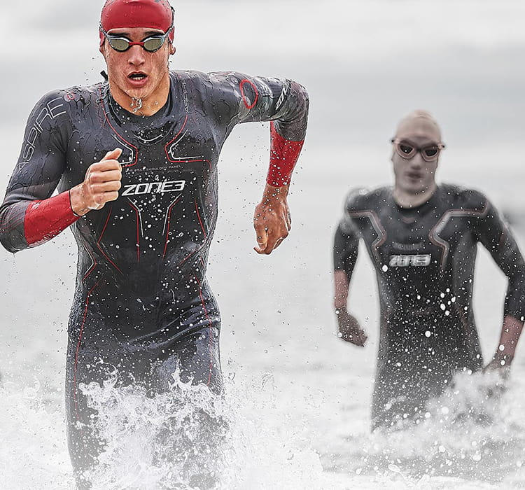 Three people coming out from their sea swim in zone3 wetsuit, hat and goggles