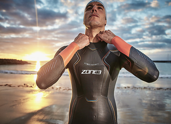 Guy on beach at sunset, wearing his Zone3 Vanquish wetsuit
