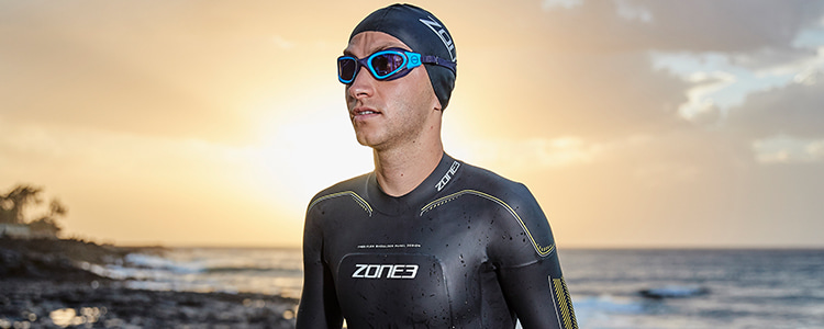 Guy on sandy beach wearing Zone3 Vision wetsuit